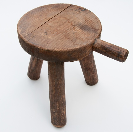 stool: This hand made milking stool has seen years of heavy use   It has a handle attached to the seat according to traditional design
