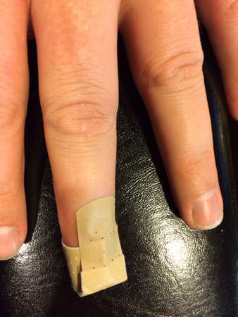 Fingers with a band aide on the middle finger