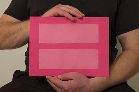 hombre sentado: hombre sentado sostiene signo de igualdad Foto de archivo