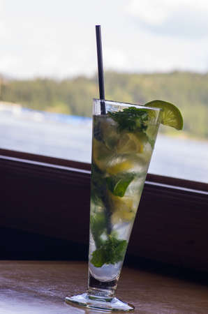 lime mint mojito on wooden table with window in the background   photo