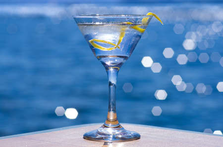 Gin or vodka martini with a twist and the lake in background.
