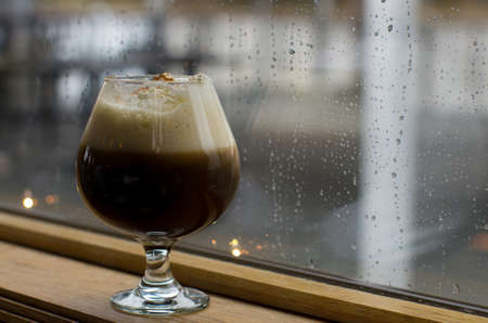 snifter: Coffee cocktail in snifter with a rainy window in background Stock Photo