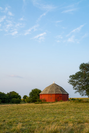 Red round barn in the open field in the late afternoon light.  LaSalle County, Illinois, USA