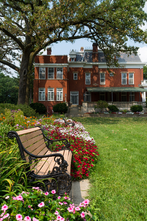 Bench and garden with the historic Ellwood House in the background.  Dekalb, Illinois, USA