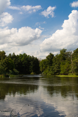 Blue skies and clouds over the DuPage River on a Summer morning.  Channahon State Park, Illinois, USA