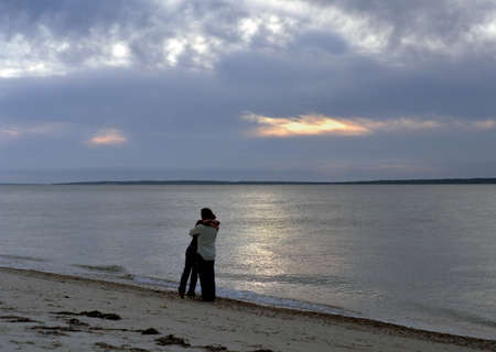 early 30s: young love at sunset - a couple embracing on the beach under a threatening sky.