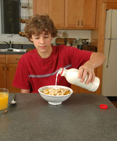 Boy pouring milk on cereal photo