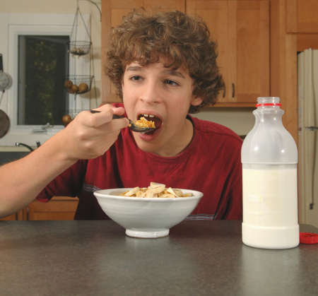 eager: boy eating cereal Stock Photo