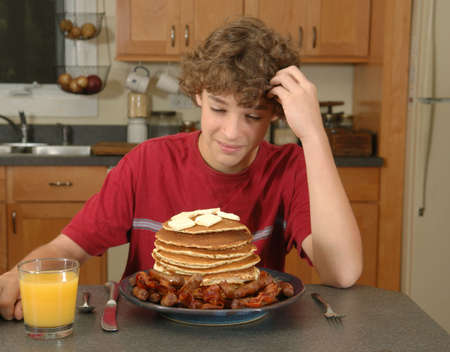 boy ponders huge pancake breakfast photo
