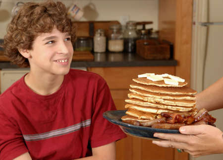 Mother serves delighted son enormous breakfast