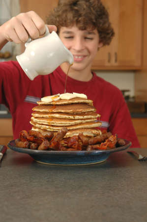 Boy pouring syrup on huge stack of pancakes