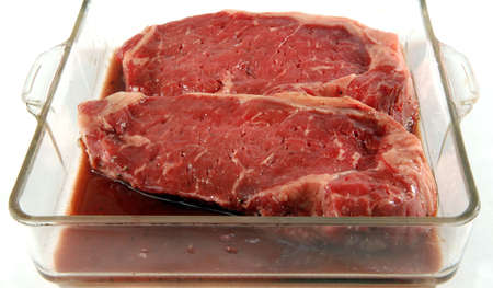 broiling: two steaks marinating in ovenware dish