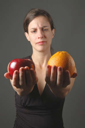 business skeptical: young woman holding apple and orange - no comparison!