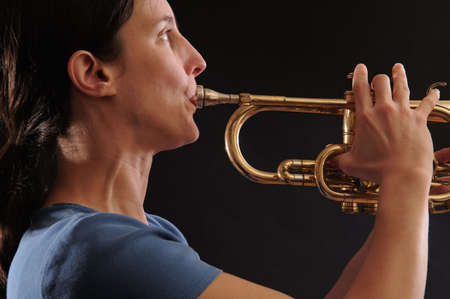 profile, woman playing trumpet, black background