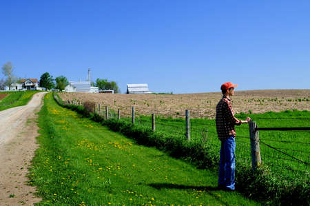 Young farmer looking past his fence