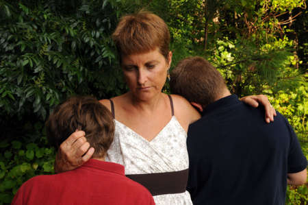 Mother, perhaps single parent, comforting sons photo
