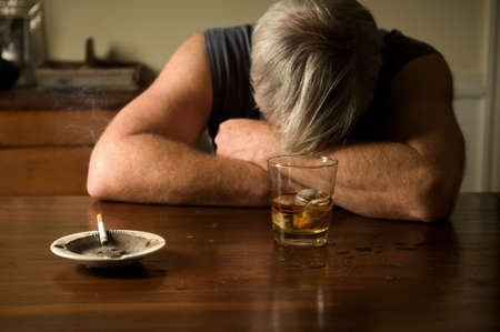 crossed cigarette: lonely alcoholic Stock Photo