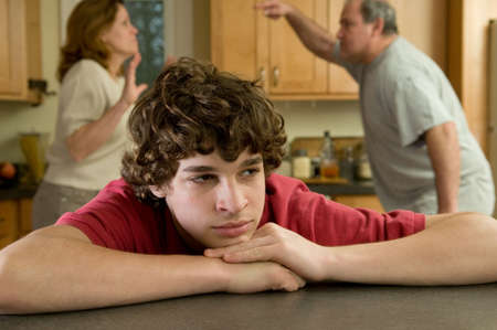 women fighting: Teen son cries while parents argue Stock Photo