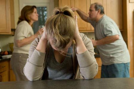 Dochter dekt oren terwijl ouders betogen Stockfoto