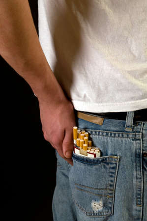 Teen smoker with cigarettes in back pocket