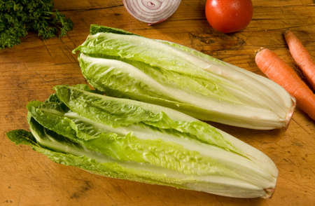 fresh romaine lettuce with veggies on old cutting board