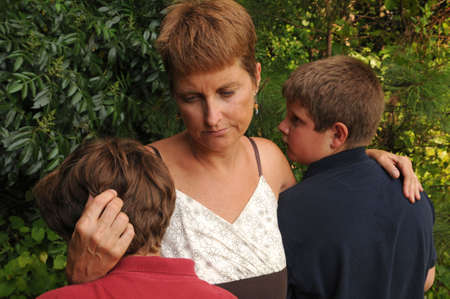 single mother comforting crying sons photo