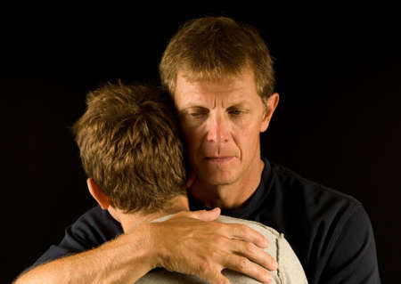 consoling: Hugging son, father cries (death, divorce, family fight, or similar) Stock Photo