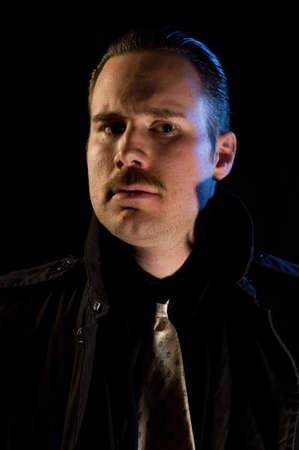 sinister man gangster criminal chiaroscuro lighting stock photo