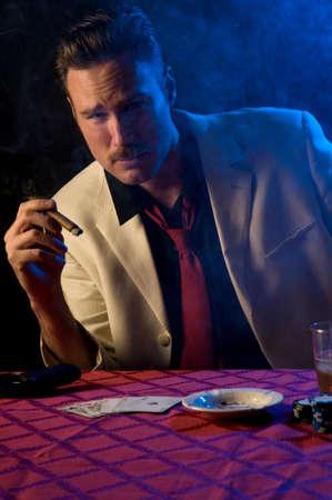 gun room: gangstergambler with gun and cigar in smoke-filled room