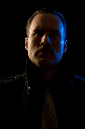 glowering: Mobstercriminalmurderer - scary-looking bad guy in trench coat with chiaroscuro film noir lighting Stock Photo