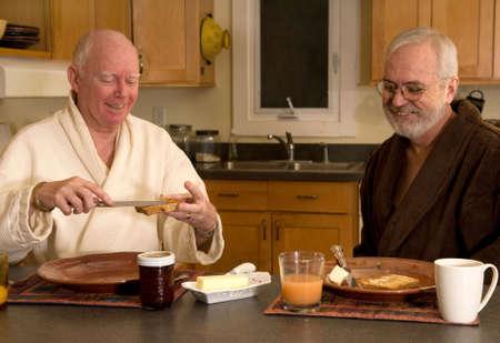 gay love: Mature married gay couple having breakfast