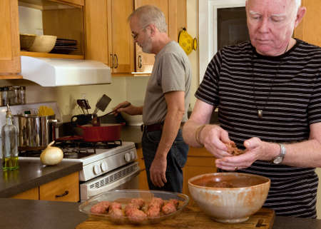 gay love: mature gay couple cooking dinner