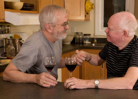 gay men: Mature married gay couple having wine and showing affection Stock Photo
