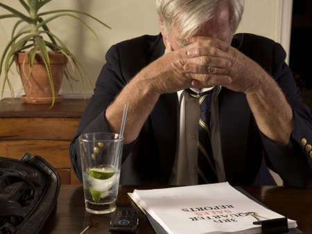 Businessman with bad sales report, drinking alone, showing frustration and anxiety 版權商用圖片