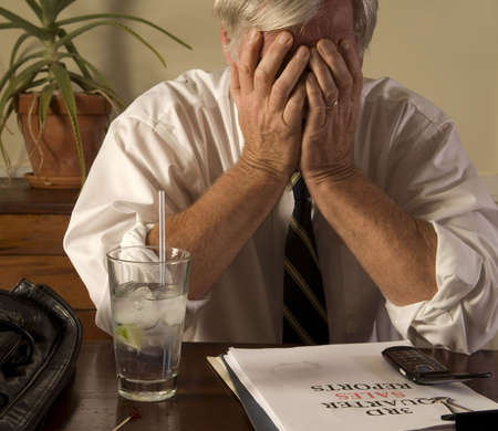 travelling salesman: Businessman with bad sales report, drinking alone, showing frustration and anxiety Stock Photo