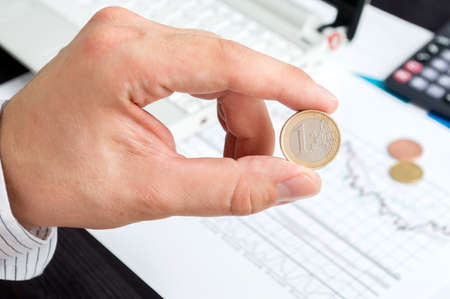 expenditure: Man holds one euro coin. Conception of capital expenditure and budgeting control.