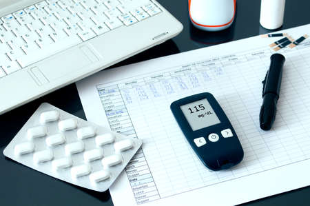 ambulatory: Blood glucose meter lying on a blood sugar diary. Conception of blood glucose testing.
