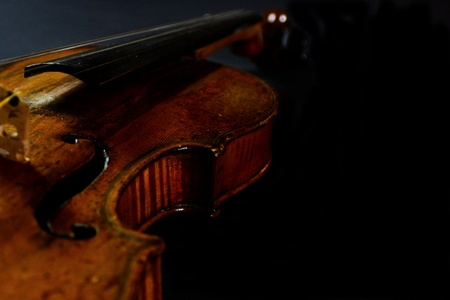 An antique wood worn violin with focus on the waist, sitting in the dark