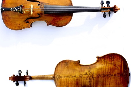 stringed: An antique wood worn violin with view of front and ornate back Stock Photo