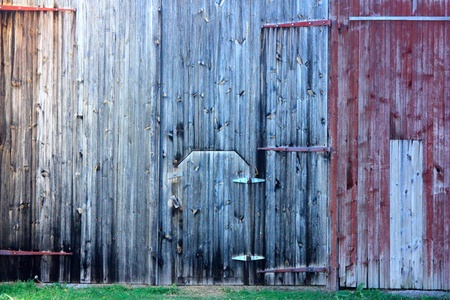 An old weathered gray wooden barn door through a weathered wwood barn
