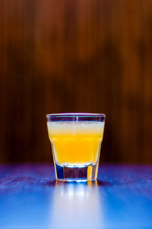 Cocktail shot with tequila, orange juice and syrup.