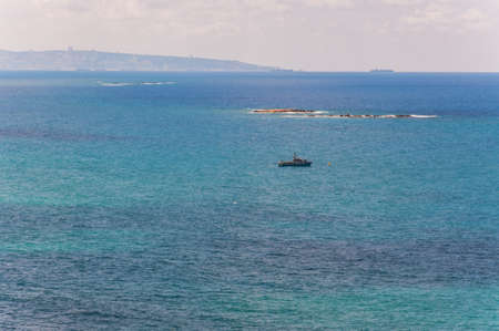 Rosh Hanikra, Israel - May 20, 2012: View on patrolling Israeli army sea ship in Mediterranean Sea bay with Haifa cityscape on the background