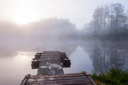 Morning sunrise fog above forest lake and pier
