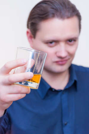 Portrait of young Caucasian Ethnicity man with blue shirt showing offering glass of whiskey brandy on white background.