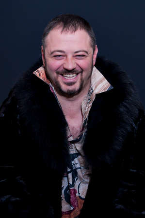 Studio portrait of happy positive laughing young bearded man with colored vibrant shirt and black fur coat