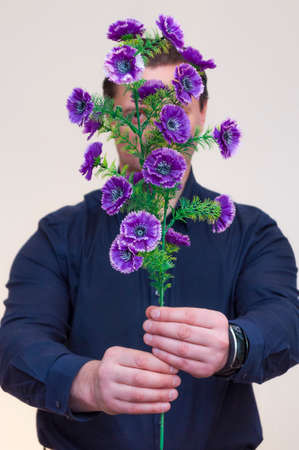 Portrait of young athletic elegant man holding artificial violet Centaurea flowers in front of his face and hiding behind it.