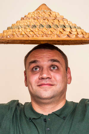 Human face can be different with strong expressions and emotions. Surprised man looking up on straw hat above his head.