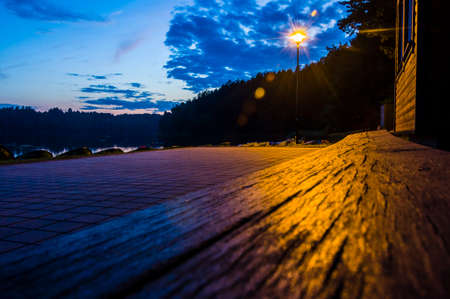 Lake beach bench by sidewalk at night illuminated with street lantern. Lantern had use in human life for a very long time. Stock Photo