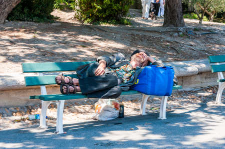 Avignon, France - July 24, 2011: Homeless man is sleeping oudoors in Old Town with knife under the bench during Avignon Festival Off. Close to him people are resting, sitting, walking by. Editorial