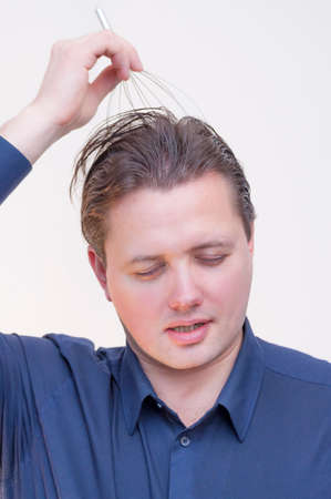 Portrait of young elegant Caucasian Ethnicity man that is enjoying of making head scalp self-massage with anti-stress device on white background.